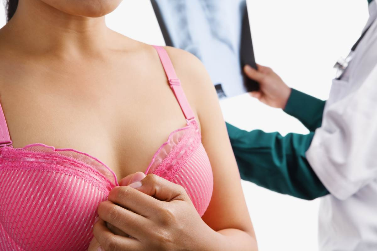 Woman on pink bra waiting nervously doctor examine xray result in background
